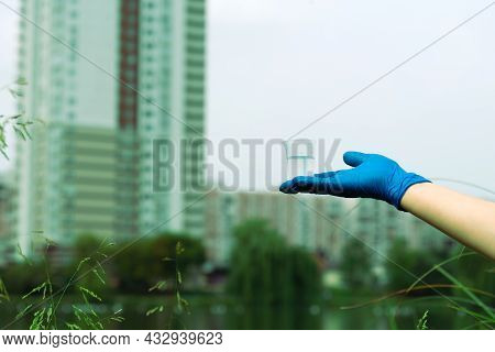 A Gloved Hand Holds A Beaker With A Sample Of Water. Sampling From Open Water. Scientist Or Biologis