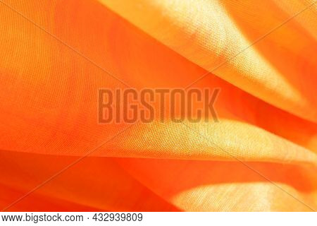 Background From Material Of Yellow-orange Color. Fabric With Pleats And Waves. Light Orange Tint Pat