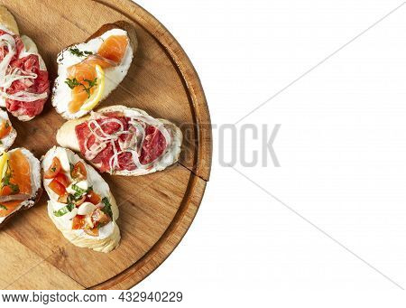 Assorted Canapes On A Wooden Board. Delicious Snacks. Isolated On White Background. Space For Text.