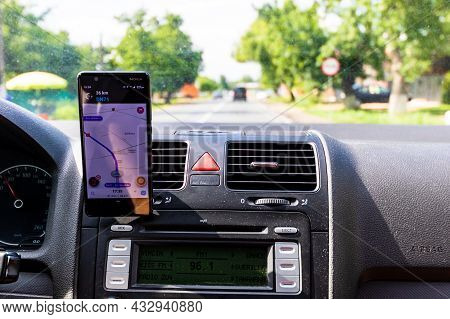 Driving And Using Waze Maps Application On Smartphone On Car Dashboard,  Bucharest, Romania, 2021