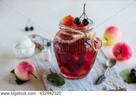Apple Jam With Apple Pieces And Chokeberry In A Jar On A Light Concrete Background. Jam Recipes. Can