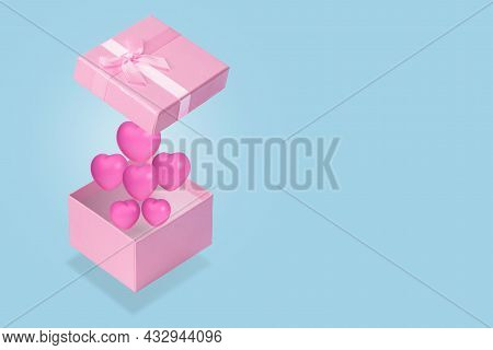 Hearts Come Out Of A Pink Gift Box On Blue Background.