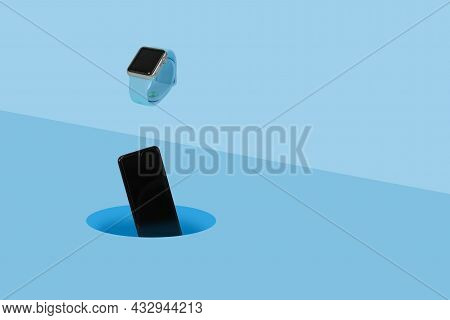Smart Watch And Mobile Phone Falling Into A Hole On Pastel Blue Background.
