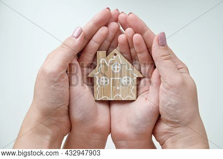 A Woman And Child Are Holding A Wooden House In Their Hands. Mom And Daughter Holds House Figurine.