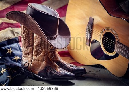 Country music festival live concert with acoustic guitar, antique american flag, cowboy hat and boots