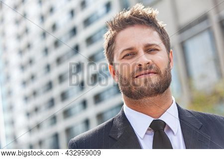 Young successful man, male executive businessman wearing suit and tie, in front of a high rise office block in a modern city