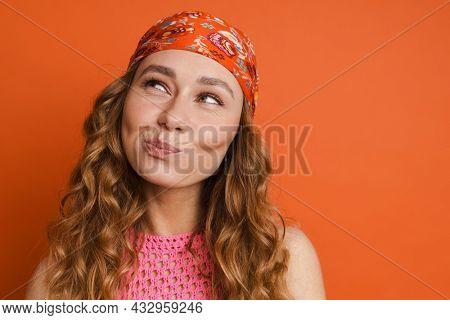 Young ginger woman wearing bandana grimacing and looking upward isolated over orange wall