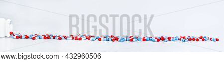 Heap Of Colorful Painkiller Pills Lay In Long Line On White Table Background With Copy Space. Blue-r