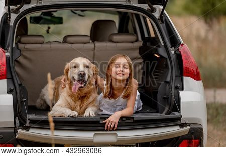 Pretty little girl with golden retriever dog lying in car trunk together and looking at camera. Cute child kid resting with doggy pet in vehicle