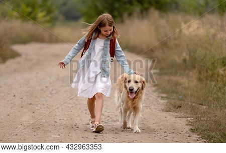 School girl with backpack and golden retriever dog running in the field. Preteen child kid with doggy pet at nature together