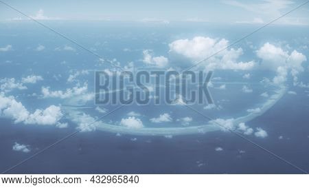 Aerial View Of A Huge Round Coral Island Surrounded By Blue Ocean Water, With Plenty Of Small Strato