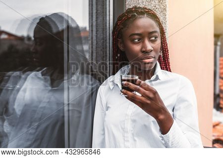 A Portrait Of A Young Dazzling Black Woman With Red Braids And In A White Shirt, Leaning Against A G