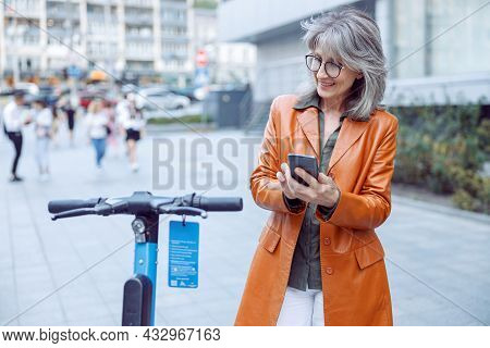 Senior Woman With Glasses And Mobile Phone Looks At E-scooter Exposed On City Street