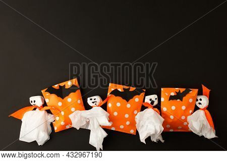 Halloween Holiday Concept With Party Gift Paper Bag Decor And Papercraft Ghosts On Black Backgtound,