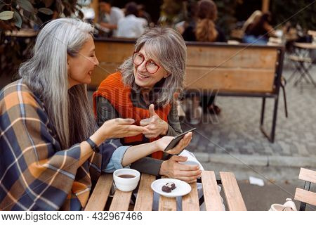Smiling Senior Woman Shows Thumb Up To Friend Holding Cellphone In Street Cafe