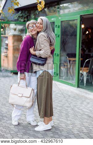Cheerful Senior Asian Lady With Grey Haired Friend Hug Meeting On Modern City Street