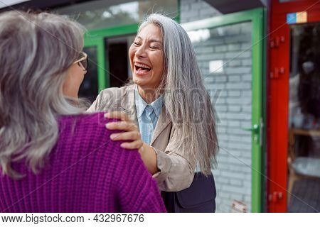 Emotional Mature Asian Lady Laughs Meeting Grey Haired Best Friend On Modern City Street