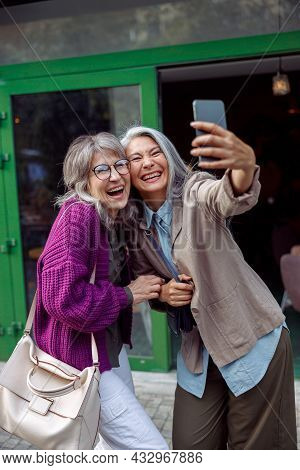Beautiful Laughing Mature Asian Lady With Companion Take Selfie With Smartphone On City Street