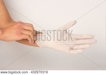 Hand Are Wearing White Rubber Gloves And Pulling Isolated On White Background,  Gloves Protect Hands