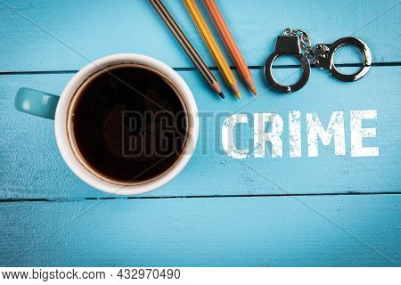 Crime, Law, Investigation And Court Concept. Coffee Mug And Miniature Handcuffs On A Wooden Table