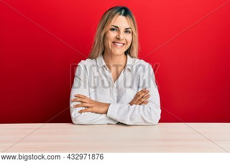 Young caucasian woman wearing casual clothes sitting on the table happy face smiling with crossed arms looking at the camera. positive person.