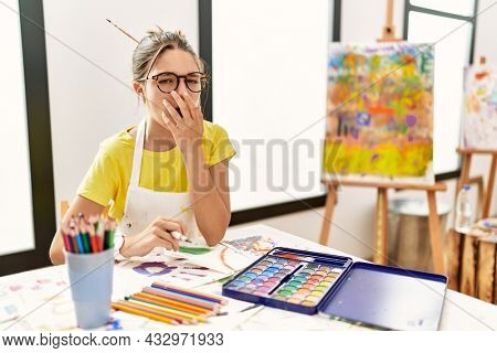 Young brunette teenager at art studio bored yawning tired covering mouth with hand. restless and sleepiness.