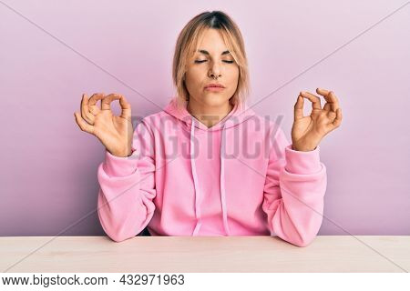 Young caucasian woman wearing casual clothes sitting on the table relax and smiling with eyes closed doing meditation gesture with fingers. yoga concept.