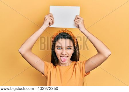 Young brunette girl holding blank empty banner over head sticking tongue out happy with funny expression.