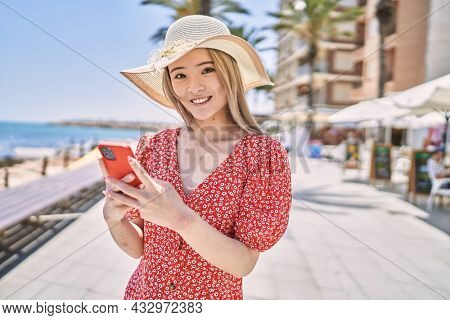 Young chinese girl wearing summer hat using smartphone at the promenade.