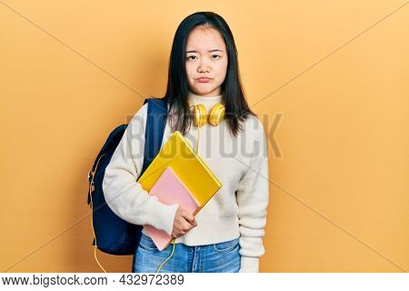 Young chinese girl holding student backpack and books depressed and worry for distress, crying angry and afraid. sad expression.