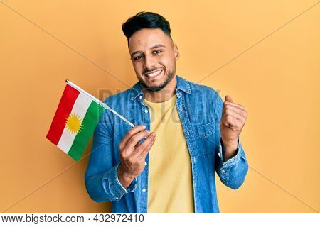 Young arab man holding kurdistan flag screaming proud, celebrating victory and success very excited with raised arm