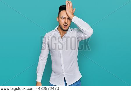 Young arab man wearing casual clothes surprised with hand on head for mistake, remember error. forgot, bad memory concept.