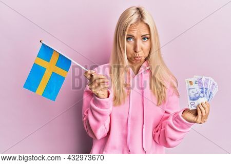 Young blonde woman holding sweden flag and krone banknotes depressed and worry for distress, crying angry and afraid. sad expression.