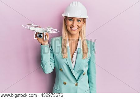 Young blonde woman wearing architect hardhat holding drone looking positive and happy standing and smiling with a confident smile showing teeth