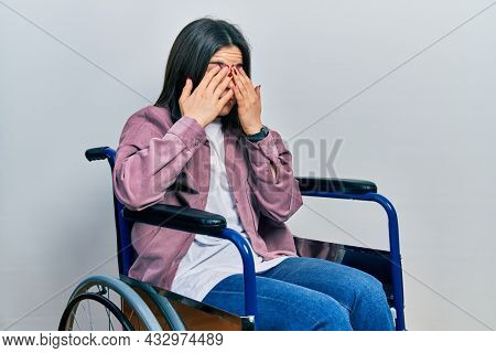 Young brunette woman sitting on wheelchair rubbing eyes for fatigue and headache, sleepy and tired expression. vision problem