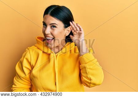 Beautiful brunette woman wearing casual sweatshirt smiling with hand over ear listening and hearing to rumor or gossip. deafness concept.