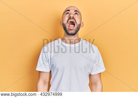 Young bald man wearing casual white t shirt angry and mad screaming frustrated and furious, shouting with anger. rage and aggressive concept.