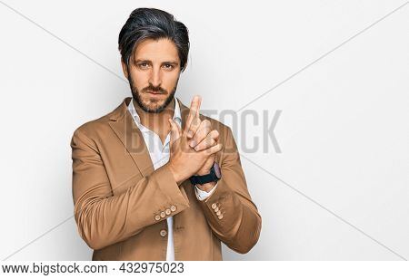 Young hispanic man wearing business clothes holding symbolic gun with hand gesture, playing killing shooting weapons, angry face