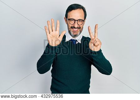 Middle age hispanic man wearing casual clothes and glasses showing and pointing up with fingers number seven while smiling confident and happy.