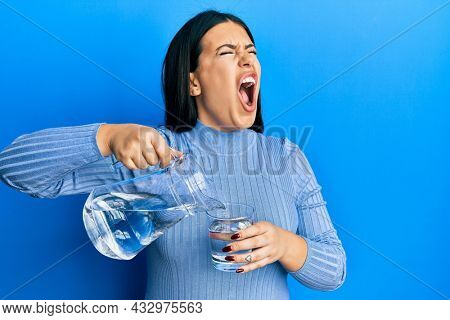 Beautiful brunette woman pouring water in glass angry and mad screaming frustrated and furious, shouting with anger. rage and aggressive concept.