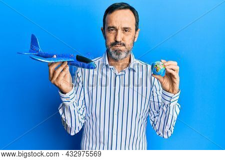 Middle age hispanic man holding plane toy and world ball puffing cheeks with funny face. mouth inflated with air, catching air.