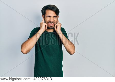 Young hispanic man wearing casual white tshirt covering ears with fingers with annoyed expression for the noise of loud music. deaf concept.