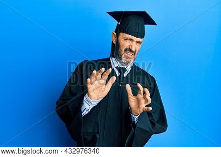 Middle age hispanic man wearing graduation cap and ceremony robe disgusted expression, displeased and fearful doing disgust face because aversion reaction. with hands raised