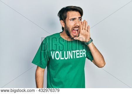 Young hispanic man wearing volunteer t shirt shouting and screaming loud to side with hand on mouth. communication concept.
