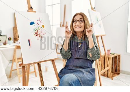 Middle age artist woman at art studio gesturing finger crossed smiling with hope and eyes closed. luck and superstitious concept.
