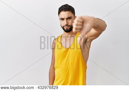 Young handsome man with beard standing over isolated background looking unhappy and angry showing rejection and negative with thumbs down gesture. bad expression.
