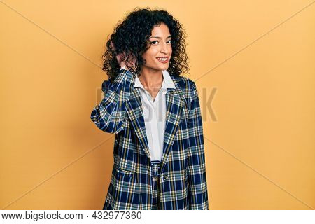 Young latin girl wearing business clothes smiling with hand over ear listening an hearing to rumor or gossip. deafness concept.