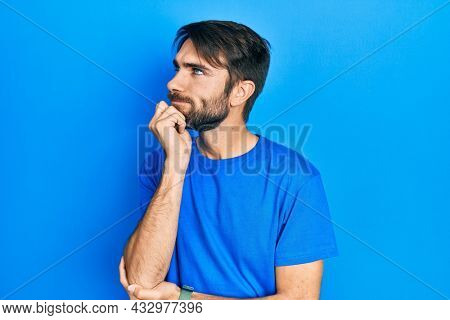 Young hispanic man wearing casual clothes with hand on chin thinking about question, pensive expression. smiling and thoughtful face. doubt concept.