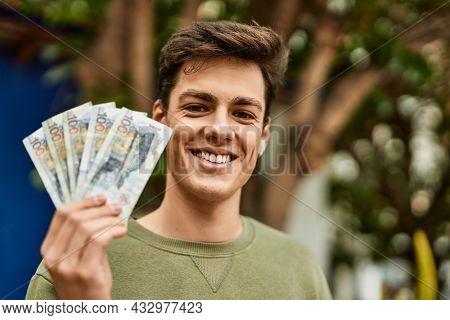Young hispanic man smiling happy holding peruvian soles banknotes at the city.