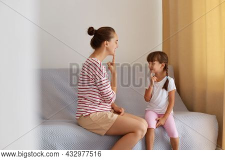 Indoor Shot Of Woman With Hair Ban Sitting On Sofa With Little Girl, Demonstrating For Child How To